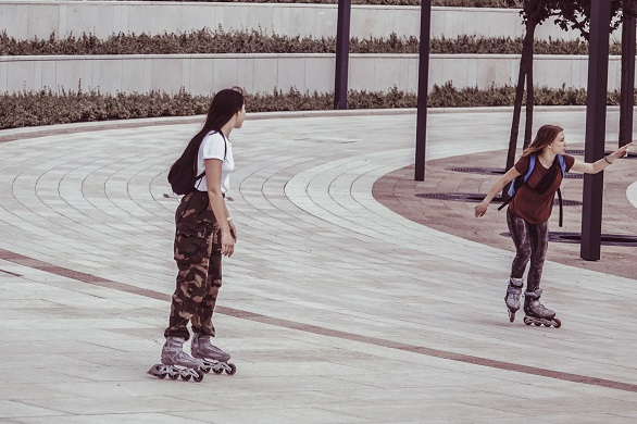 picture of two girls on roller blades in a park