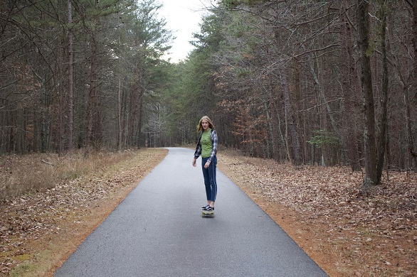 picture of a girl on a skateboard in the woods