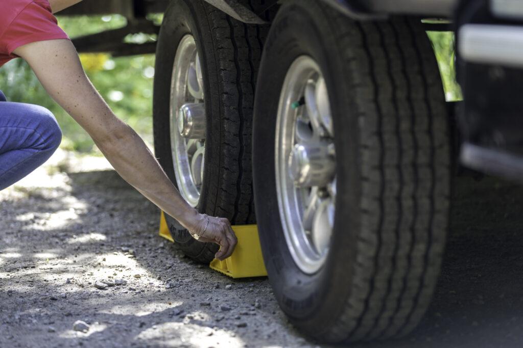 Woman Putting Tire Blocks on Camper Trailer