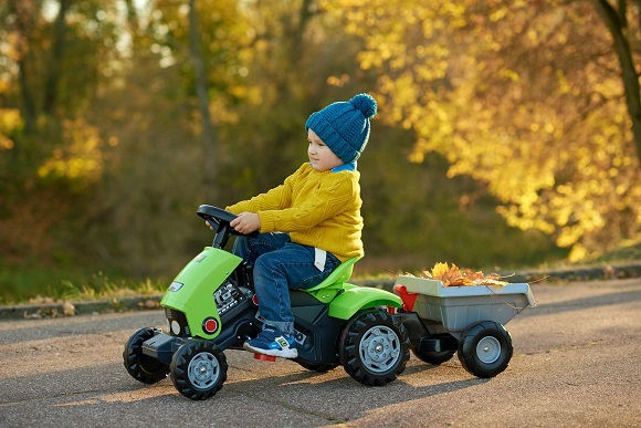 picture of a baby boy playing with a plastic tractor on an alley picking up leaves