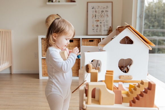 picture of a baby kid playing with wooden toys in a room with a view of nature