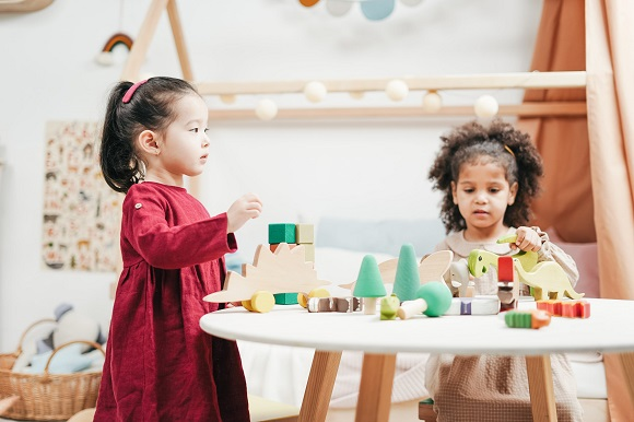 picture of two girls playing with wooden toys