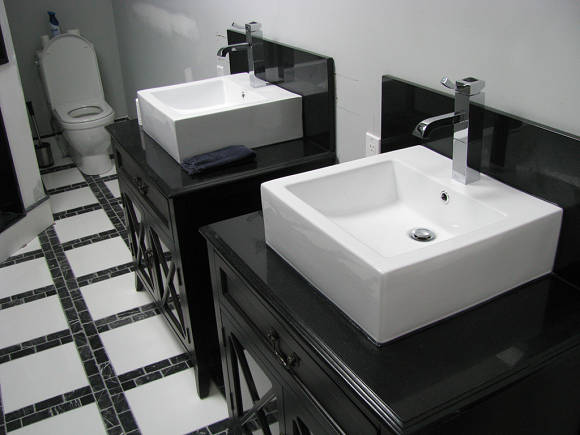 two white and black bathroom sinks