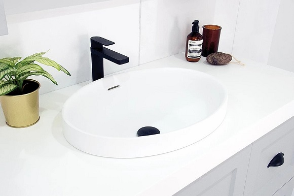 white sink with flower and soaps on it