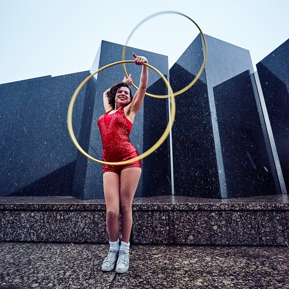 picture of a woman in unitard in front a statue holding hula hoops