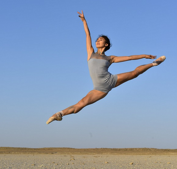 picture of a woman on a sand dancing in the air wearing blue leotards
